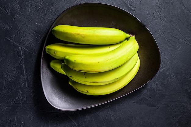 Bananes vertes sur une plaque. vue de dessus. fruit exotique