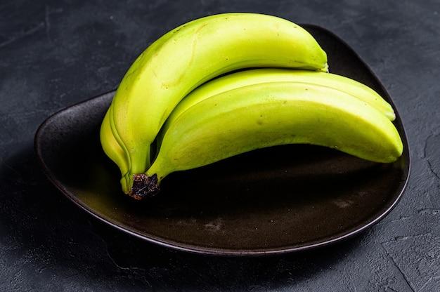 Bananes vertes sur une plaque