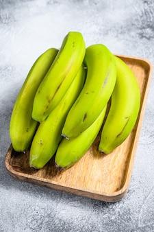 Bananes vertes sur un plateau en bois.