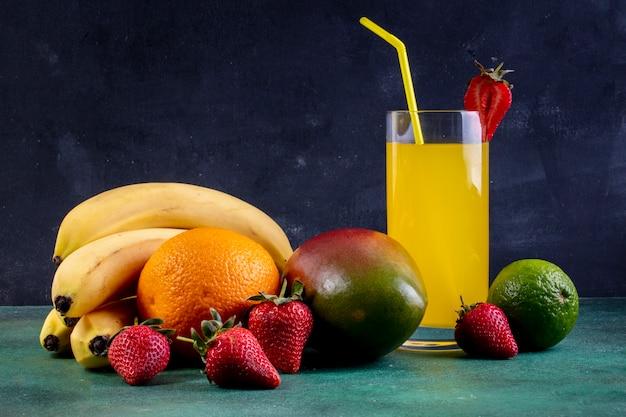 Bananes vue de face avec mangue orange fraise citron vert et un verre de jus d'orange