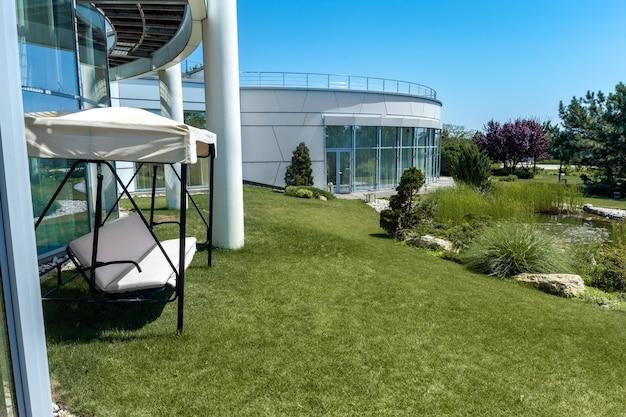 Banc de balançoire de jardin avec auvent près du manoir sur fond de jardin paysager bien entretenu en été