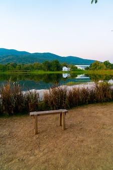 Banc En Bois Avec Beau Lac à Chiang Mai Avec Montagne Boisée Et Ciel Crépusculaire En Thaïlande . Photo Premium