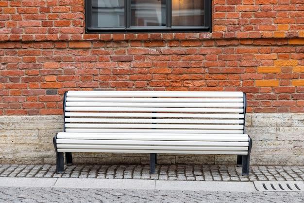 Banc en bois blanc vide solitaire avec vieux mur de briques brunes et fenêtre noire