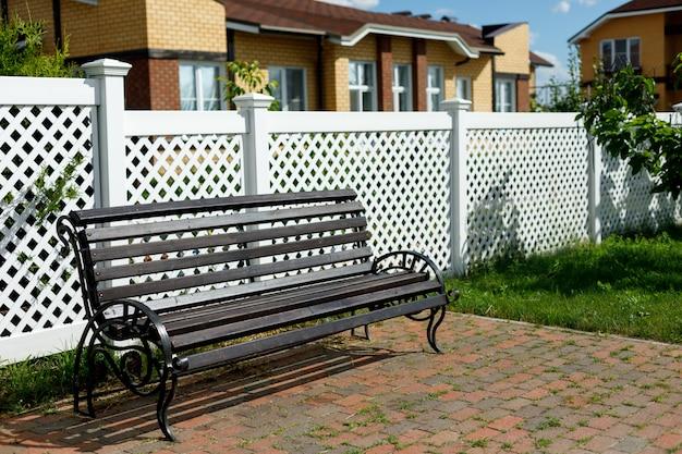 Banc en bois et clôture en plastique blanc dans un village de campagne