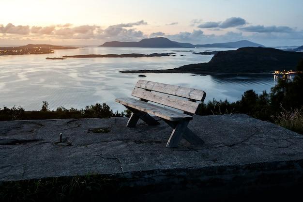 Un banc en bois isolé se dresse au sommet d'une montagne. coucher de soleil le soir