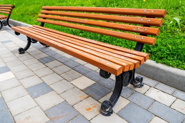 Banc en bois avec des jambes de fer dans un parc par une journée ensoleillée en été