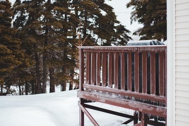 Banc en bois marron sur sol couvert de neige
