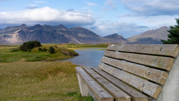 Banc en bois sur la prairie avec vue magnifique sur la montagne