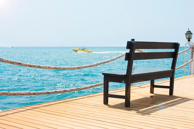 Banc en bois sur le quai au bord de la mer avec un bateau