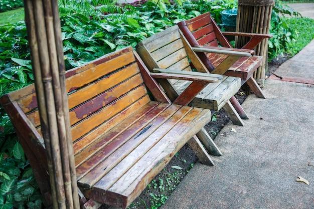 Banc et chaises en bois de conception paysagère architecturale près d'un jardin d'herbe verte en public