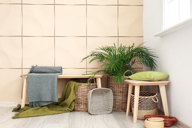 Banc avec paniers en osier et plante d'intérieur dans la chambre