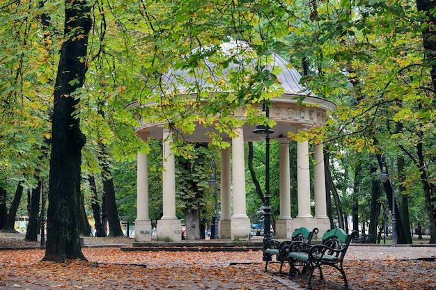Banc de parc à l'automne sur fond d'arches blanches