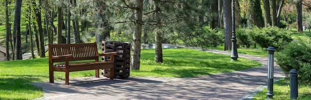 Banc de parc sous un arbre à l'ombre. poubelle près du banc. sentier pour une promenade dans le parc ensoleillé au printemps.