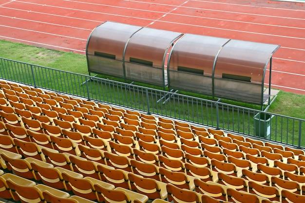 Bancs de coach et de réserve avec sièges jaunes dans un stade de football