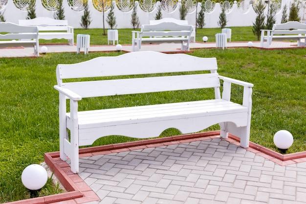 Bancs vides en bois blancs dans le parc de la ville.
