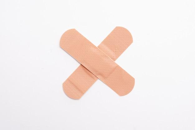 Band-aids formant un x ou une croix sur blanc