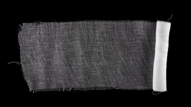 Bandage médical isolé sur une surface noire.