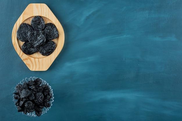 Bande d'abricots secs, de prunes et de raisins secs sur table bleue.