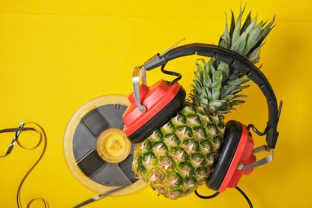 Bande audio magnétique et ananas dans un casque rétro rouge sur fond jaune, vue de dessus