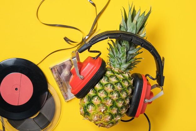 Bande audio magnétique, vinyle et ananas dans un casque rétro rouge sur fond jaune, vue de dessus