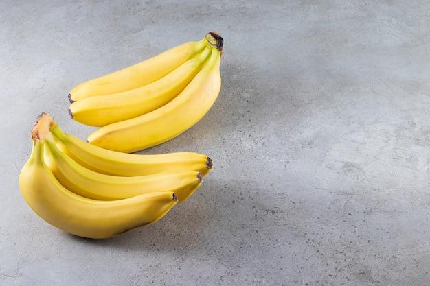 Bande de banane jaune juteuse placée sur une surface en pierre