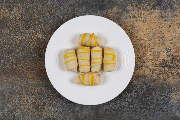 Bande de biscuits crémeux sur plaque blanche.