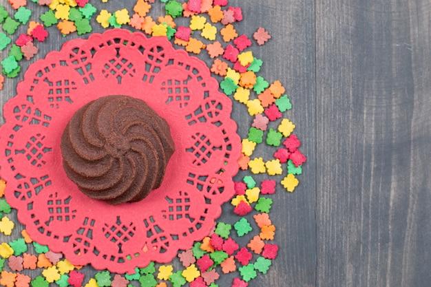 Bande de bonbons colorés autour d'un biscuit au chocolat
