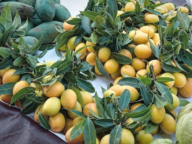 Bande de fruits jaunes avec des feuilles vertes en vente à market stall