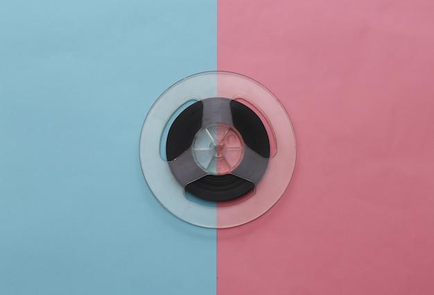 Bande magnétique audio. bobine de film sur pastel bleu rose. style rétro. minimalisme
