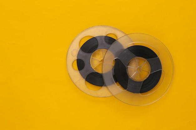 Bande magnétique audio. deux bobines de film sur jaune. style rétro