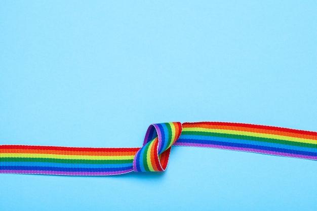 Bande avec un nœud. ruban arc-en-ciel de fierté lgbt sur fond bleu.