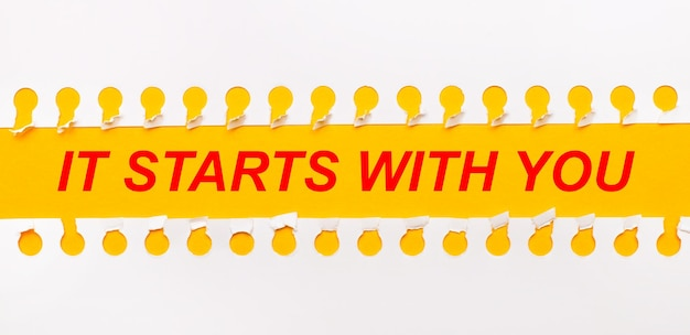 Bande de papier déchiré sur fond jaune avec texte ça commence avec vous