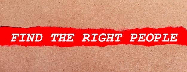 Une bande de papier rouge sous le papier brun déchiré. lettrage blanc sur papier rouge trouvez les bonnes personnes. vue d'en-haut