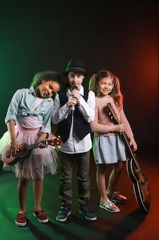 Bande de petits musiciens sur mur sombre
