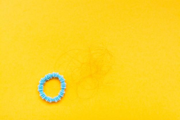 Bande pour cheveux et écailles de cheveux tombés fond jaune