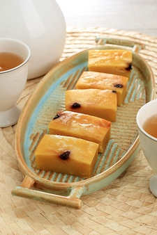 Bande de prol maison ou bolu tapai sur plaque blanche. prol tape est un gâteau traditionnel d'indonésie, fabriqué à partir de manioc fermenté, garni de fromage râpé et cuit au four