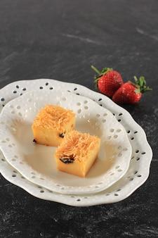 Bande de prol maison en tranches ou bolu tapai sur plaque blanche. prol tape est un gâteau traditionnel d'indonésie, fabriqué à partir de manioc fermenté, garni de fromage râpé et cuit au four. espace de copie
