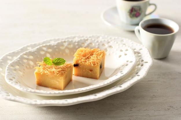 Bande de prol maison en tranches ou bolu tapai sur plaque blanche. prol tape est un gâteau traditionnel d'indonésie, fabriqué à partir de manioc fermenté, garni de fromage râpé et cuit au four
