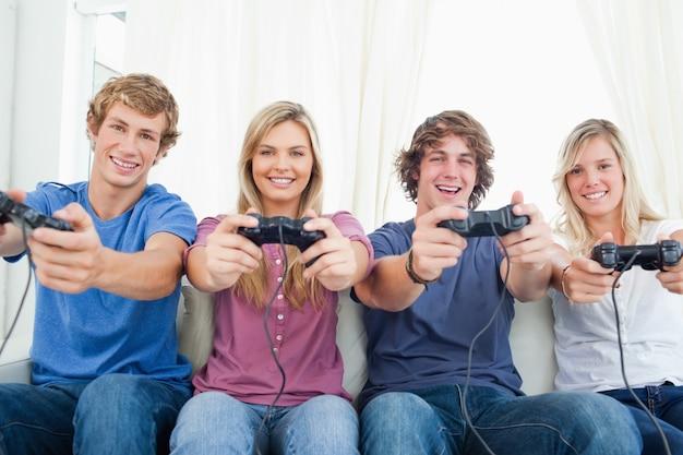 Une bande souriante d'amis qui regardent la caméra en jouant