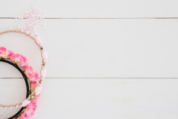 Bandeau pour les cheveux fait main rose et perles sur un bureau en bois blanc