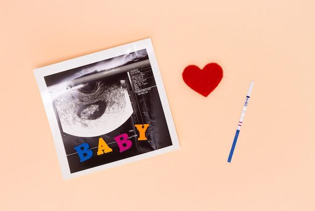 Une bandelette de test de grossesse positive, une image échographique du fœtus, un cœur rouge et l'inscription