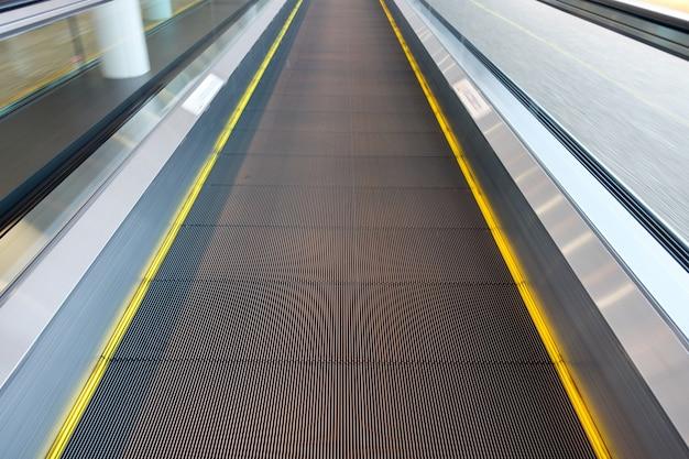 Bandes jaunes d'escalator se déplaçant vers l'avant dans l'aéroport