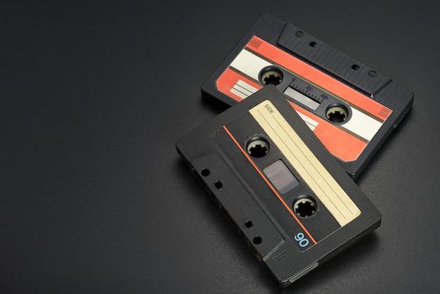 Bandes avec musique. deux vieilles cassettes compactes audio noires sur fond noir