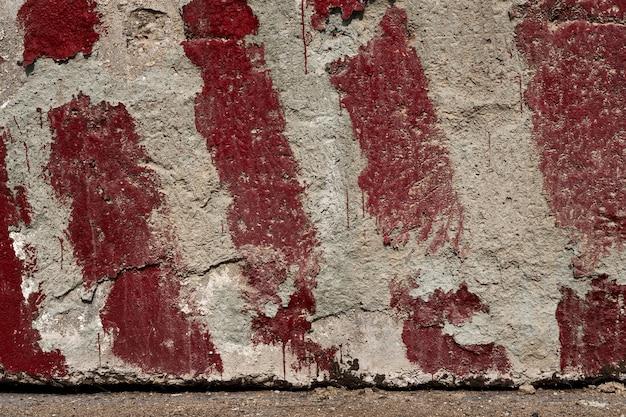 Bandes rouges peintes sur le béton comme un avertissement et une indication de la taille et des limites comme arrière-plan ou texture
