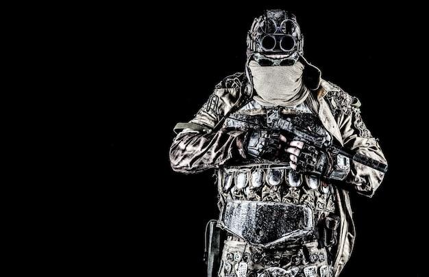 Bandit ou maraudeur du monde post-apocalyptique, survivant d'une catastrophe nucléaire, harceleur vétéran en masque facial et lunettes de soleil, armure lamellaire artisanale, armé d'un pistolet fait main, isolé sur un tournage en studio noir