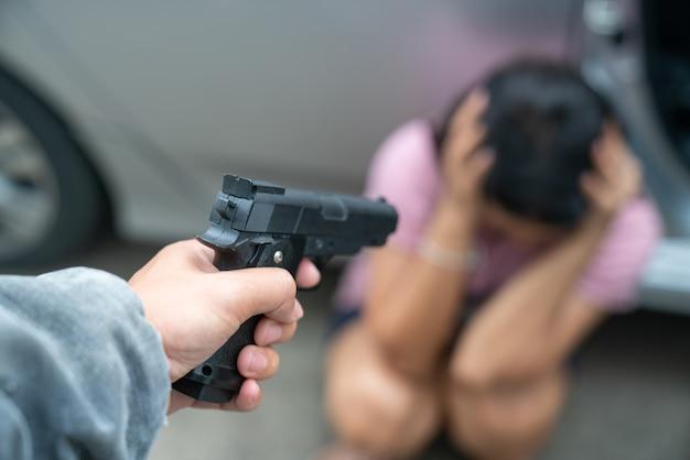 Un bandit porte un masque noir et des vêtements noirs à l'aide d'un pistolet