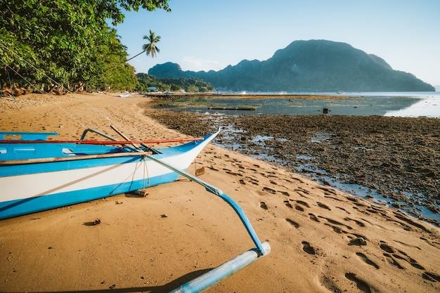 Bangka banca bateau sur la plage de sable à distance éclairée par la lumière du coucher du soleil d'or. village d'el nido. philippines.