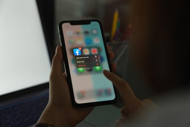 Bangkok, thaïlande - 14 avril 2020: la main tient le téléphone et supprime l'écran facebook sur l'iphone d'apple, les médias sociaux utilisent pour le partage d'informations et le réseautage.