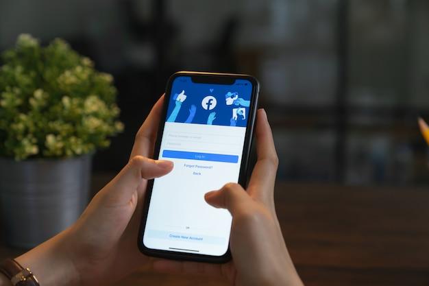 Bangkok, thaïlande - 30 mars 2020: main tient le téléphone et l'écran facebook sur l'iphone d'apple, les médias sociaux utilisent pour le partage d'informations et le réseautage.