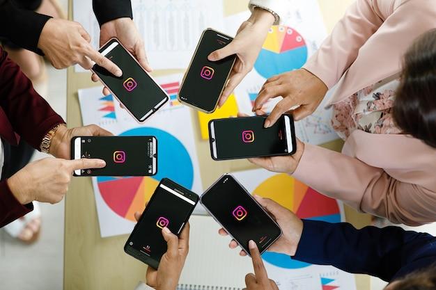 Bangkok/thaïlande - 6 août 2021 : les gens détiennent des smartphones de différentes marques et divers systèmes d'exploitation avec des logos d'applications sociales instagram.